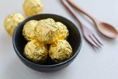 Schokoladenball mit goldener Folie in einer schwarzen Schale Lizenzfreie Stockfotografie