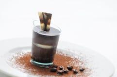 Schokoladencreme im Schmecker, Schokoladenwüste auf weißer Platte mit Kaffeebohnen und Kakaopulver, Konditorei, Fotografie für Sh Stockfotos