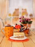 Schokoladencremekuchen, Schalentee, Scheibe, Kerze auf Hintergrundküche Stockfoto