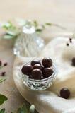 Schokoladendragée in einer Glasschüssel auf pfirsichfarbenem Stoff Stockfotografie