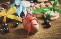 Schokoladeneier in den mehrfarbigen Bändern auf einem Holztisch Stockfotografie