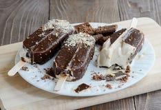 Schokoladeneis am stiel auf einem hölzernen Hintergrund Lizenzfreie Stockbilder