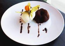 Schokoladenfondant mit einer Schaufel der Sahneeiscreme und des Physalis stockbild