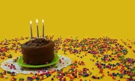 Schokoladengeburtstagskuchen mit 3 blau und weißen Kerzen beleuchtete, auf einer kleinen grünen Platte, umgeben durch die Süßigke Stockbild