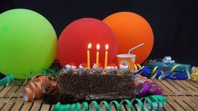 Schokoladengeburtstagskuchen mit drei gelben Kerzen, die auf rustikalem Holztisch mit Hintergrund von bunten Ballonen brennen lizenzfreies stockfoto