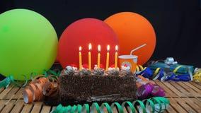 Schokoladengeburtstagskuchen mit fünf gelben Kerzen, die auf rustikalem Holztisch mit Hintergrund von bunten Ballonen brennen lizenzfreie stockbilder