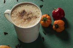 Schokoladengetränk begleitet von den Pfeffern in der weißen Schale und im grünen Hintergrund lizenzfreie stockfotos