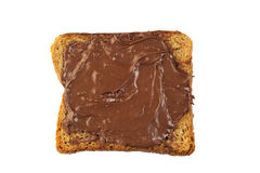 Schokoladenhaselnussverbreitung auf dem Vollweizentoast lokalisiert Lizenzfreies Stockbild