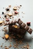 Schokoladenhaus und getrocknete Beeren mit N?ssen auf einem schwarzen Hintergrund, vertikal stockbild