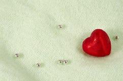 Schokoladenherz in einer roten Verpackung auf einem hellen Hintergrund mit glänzenden Perlen lizenzfreies stockfoto