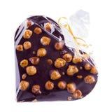 Schokoladenherz mit Haselnüssen im Plastikfilm lokalisiert Stockfotos