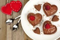 Schokoladenherz-Nachtischschalen mit Pudding und Himbeeren Stockfotografie