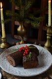 SchokoladenJulblock-Weihnachtskuchen mit Weihnachtsdekoration auf der Feiertagstabelle Stockfotos