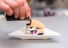 Schokoladenkeks mit einer Füllung von Beeren und von Creme, auf einer weißen Platte Lizenzfreie Stockfotos