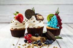 Schokoladenkleine kuchen cupcakes Kleine Kuchen mit Beeren, Frucht, strawb Lizenzfreie Stockfotos