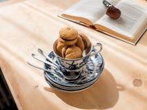 Schokoladenkleine kuchen in der Teetasse, Buch auf Hintergrund Stockfoto