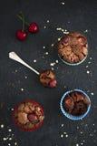 Schokoladenkleine kuchen mit Kirschen auf dunklem Hintergrund Stockbild