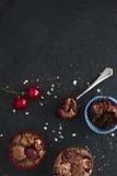 Schokoladenkleine kuchen mit Kirschen auf dunklem Hintergrund Mit Kopienraum Stockbilder