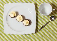 Schokoladenkleine kuchen mit Silber spritzt auf die Oberseite auf weißer Platte Stockfotografie
