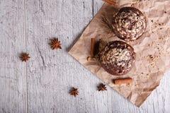 Schokoladenkleine kuchen mit Zimt auf einem hölzernen Hintergrund Kleine Kuchen mit Schokoladennachtisch Caféfrühstück Kopienraum Lizenzfreies Stockfoto