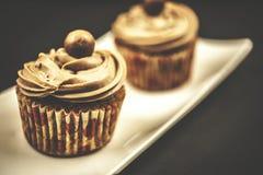 Schokoladenkleiner kuchen auf hölzernem und schwarzem Hintergrund Stockbilder