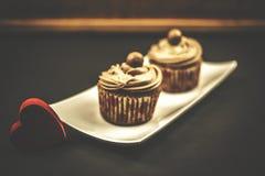 Schokoladenkleiner kuchen mit rotem hölzernem Herzen auf hölzernem und schwarzem Hintergrund Lizenzfreie Stockbilder