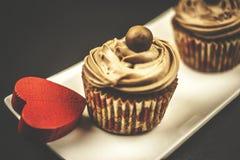 Schokoladenkleiner kuchen mit rotem hölzernem Herzen auf hölzernem und schwarzem Hintergrund Stockfotos