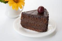 Schokoladenkuchen auf einem weißen Hintergrund mit einer Blume Lizenzfreie Stockfotos