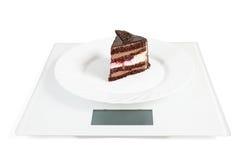 Schokoladenkuchen auf einer Platte, die auf den Skalen steht Lizenzfreie Stockfotografie