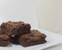 Schokoladenkuchen auf einer weißen Platte mit Milch lizenzfreie stockbilder