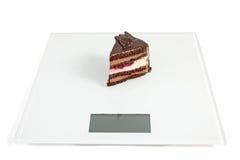 Schokoladenkuchen, der auf den Skalen steht Lizenzfreie Stockfotografie