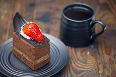 Schokoladenkuchen in der Untertasse nahe bei Becher Kaffee auf beunruhigt flehen an lizenzfreies stockbild