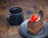 Schokoladenkuchen in der Untertasse nahe bei Becher Kaffee auf beunruhigt flehen an lizenzfreie stockfotografie