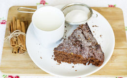 Schokoladenkuchen in einer weißen Platte und in einer Schale mit Milch Stockfotos