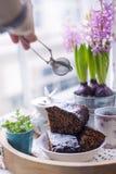 Schokoladenkuchen für Frühstück und Blumen, nahe dem Fenster Weibliche Hand auf dem Foto Freier Platz für Text Kopieren Sie Platz stockbilder