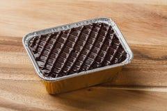 Schokoladenkuchen im Aluminiumfoliebehälter Stockbilder