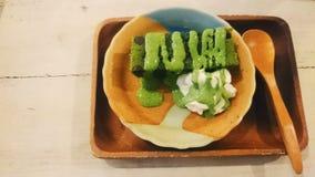Schokoladenkuchen Matcha Greentea mit Sahne und matcha Greentea-Soße auf japanischer Platte Stockbild