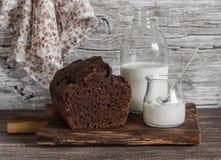 Schokoladenkuchen, Milchflasche, Jogurt auf hölzernem Hintergrund Stockbilder