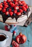Schokoladenkuchen mit Beeren und Minze auf dem Stand stockbilder