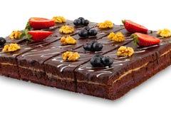 Schokoladenkuchen mit den Beeren und Nüssen lokalisiert auf weißem Hintergrund stockbild
