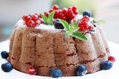 Schokoladenkuchen mit den Muttern verziert mit Früchten Stockfoto