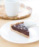 Schokoladenkuchen mit Edelstahlgabel, weißem keramischem Teller und weißer Schale im Hintergrund Stockfoto