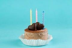 Schokoladenkuchen mit einer Kerze auf einem hellen Hintergrund Stockfoto