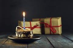 Schokoladenkuchen mit einer Kerze und Geschenken Alles Gute zum Geburtstag, Karte Vektor-roter Weihnachtstext auf grünem Hintergr Lizenzfreie Stockfotografie