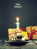 Schokoladenkuchen mit einer Kerze und Geschenken Alles Gute zum Geburtstag, Karte Vektor-roter Weihnachtstext auf grünem Hintergr Stockfotografie