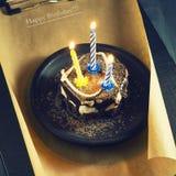 Schokoladenkuchen mit einer Kerze und Geschenken Alles Gute zum Geburtstag, Karte Vektor-roter Weihnachtstext auf grünem Hintergr Stockbild