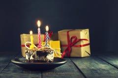 Schokoladenkuchen mit einer Kerze und Geschenken Alles Gute zum Geburtstag, Karte Vektor-roter Weihnachtstext auf grünem Hintergr Stockbilder