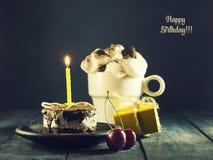 Schokoladenkuchen mit einer Kerze und Geschenken Alles Gute zum Geburtstag, Karte Vektor-roter Weihnachtstext auf grünem Hintergr Stockfotos