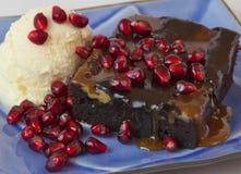 Schokoladenkuchen mit Eiscreme und Granatapfel Stockfoto