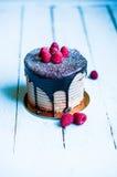 Schokoladenkuchen mit Himbeeren auf hölzernem Hintergrund Stockfoto